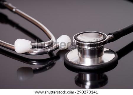 Stethoscope over a dark reflective background / Stethoscope - stock photo