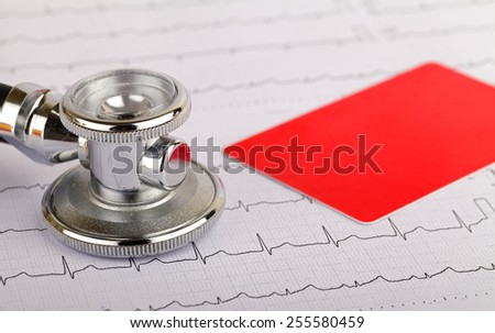Stethoscope over electrocardiogram graph and a credit card - stock photo