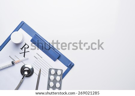 stethoscope, pills and bottles on blue medical clipboard with copy space. Medicine concept view from the top - stock photo