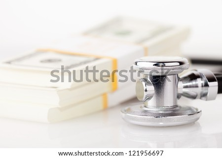 stethoscope placing on US dollar banknotes on white background