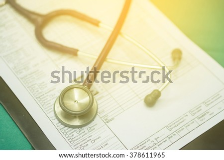 stethoscope prescribing treatment to patient for doctor with pen writing recipe on clipboard in hospital.selective focus ,and vintage tone - stock photo