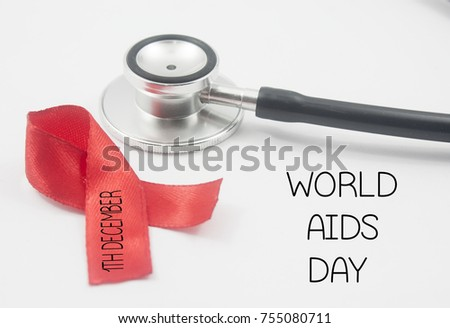 stethoscope,red ribbon written 1th december and world aids day over white background