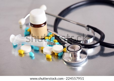 Stethoscope, syringe, pills and bottle on light background. Medicine concept - stock photo