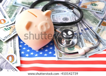 Stethoscope with dollar banknotes and piggy bank on background of USA flag - stock photo