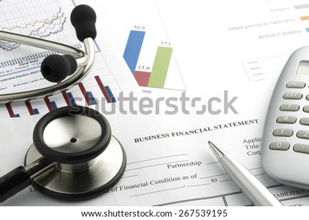 Stethoscope with financial statement, calculator, pen  - stock photo