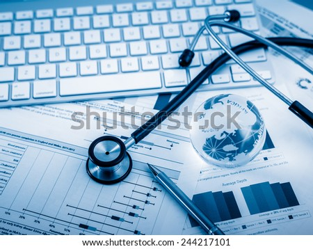 Stethoscope with financial statement on the desk. - stock photo