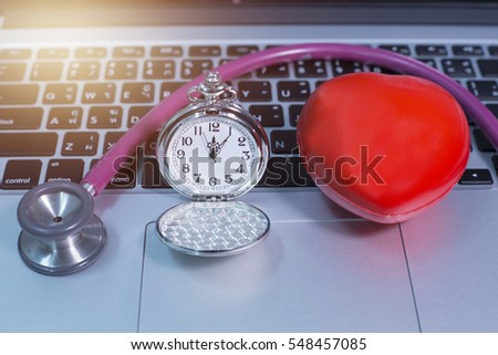 Stethoscope with heart and vintage clock on laptop with light effect.
