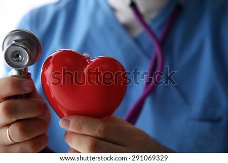 Stethoscope with heart in doctor hands, close-up - stock photo