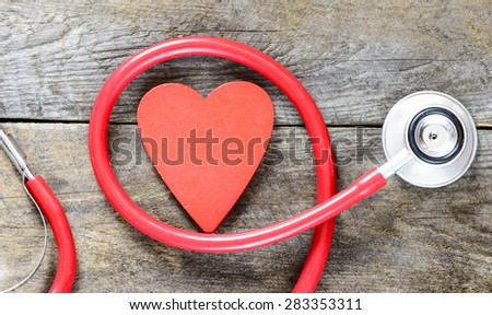 Stethoscope with heart symbol on wooden background - stock photo