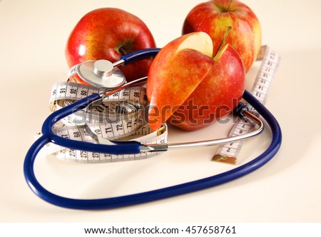 Stethoscope with red apples on a white background - stock photo
