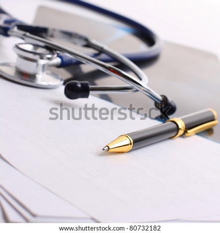 stethoscope with the handle and papers - stock photo