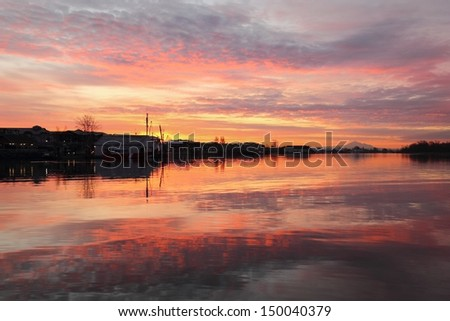 Steveston Harbor Reflected Morning Cloudscape. Sunrise colors reflect off the calm water of Steveston Harbor. Richmond, British Columbia, Canada.  - stock photo