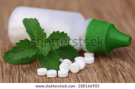 Stevia with sweetening tablets and bottle on wooden surface - stock photo