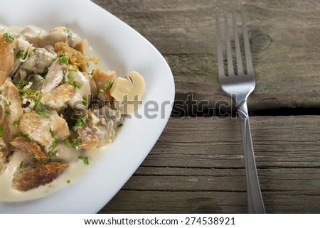 Stew chicken in a creamy sauce with mushrooms on a white plate with fork - stock photo