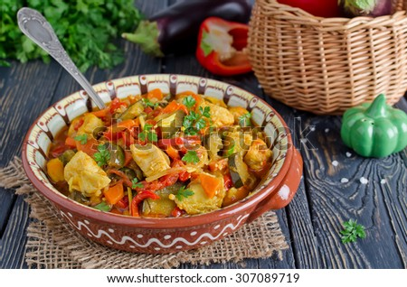 Stew with chicken and vegetables. Chicken with eggplant, bell peppers, carrots and tomatoes - stock photo