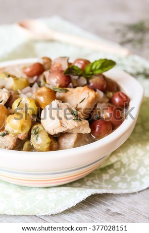 Stew with pork meat, grape, onion, basil and rosemary in a bowl, selective focus - stock photo