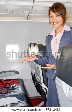 Stewardess in the empty airplane - stock photo