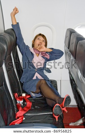Stewardess resting on a plane.Tired stewardess resting on the seat in a flying air plane. Woman in a business suit yawning seat aircraft. Yawning air hostess relaxes in a flying aircraft. - stock photo