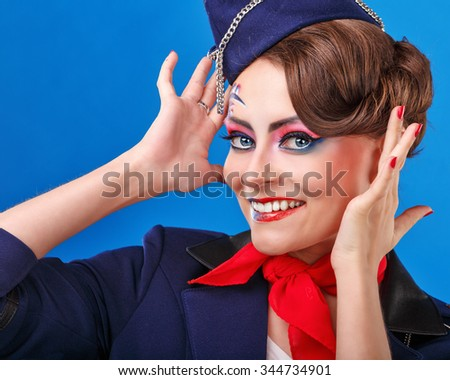 Stewardess with face art corrects hairstyle. Young attractive girl in a blue suit flight attendants. Air transportation. Service. - stock photo