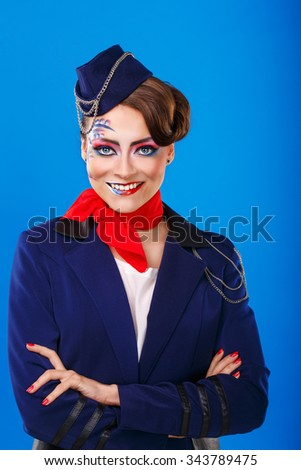 Stewardess with face art meets passengers. Young attractive girl in a blue suit flight attendants stands arms folded.