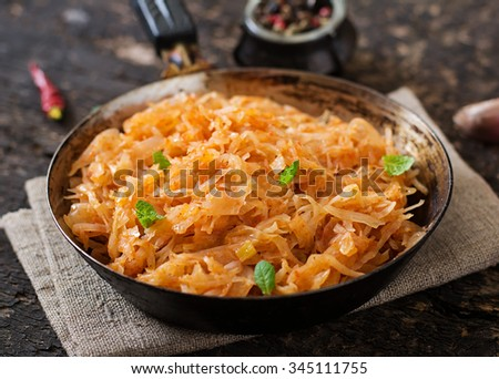 Stewed cabbage on the old wooden background in rustic style - stock photo