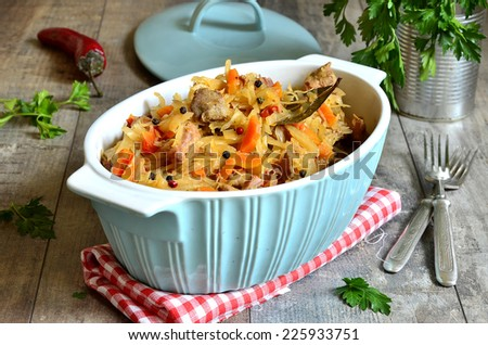 Stewed cabbage with meat on a wooden table. - stock photo