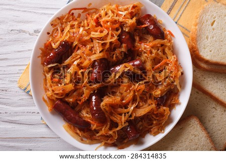 stewed cabbage with sausages close-up in white plate. horizontal view from above - stock photo