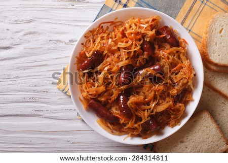 stewed cabbage with sausages in white plate. horizontal view from above
