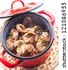 Stewed chicken gizzards in red pan on the mat - stock photo