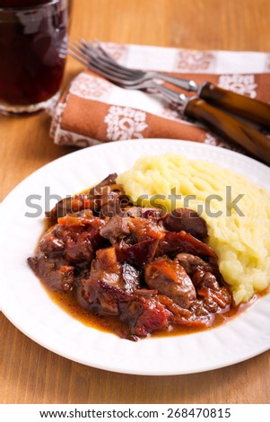 Stewed liver with plums and gravy, mashed potatoes, aside - stock photo