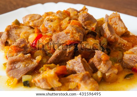 Stewed meat with vegetables in a plate on wooden table - stock photo