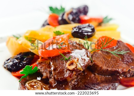 Stewed mutton with potatoes and black plums on a white plate - stock photo
