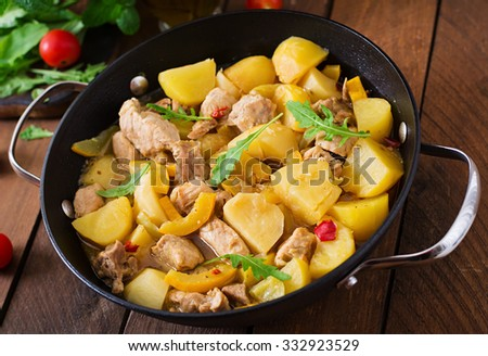 Stewed potatoes with meat and vegetables in a roasting tin on a wooden background - stock photo