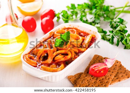 Stewed squid rings with tomato sauce in white plate - stock photo
