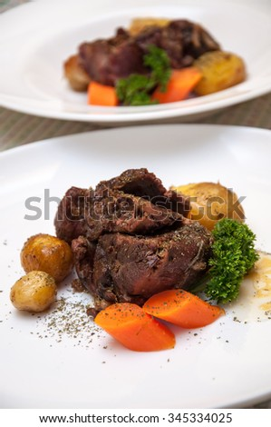 Stewed veal meat with potatoes served on plates and decorated with carrot and parsley. Selective focus, shallow dept of field. - stock photo
