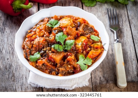 Stewed vegetables in a white bowl on wooden table - stock photo
