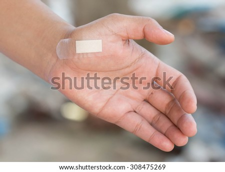 Stick a plaster on the wound in the hand. - stock photo