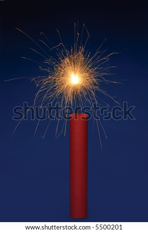 Stick of dynamite with a lit fuse on a blue background - stock photo