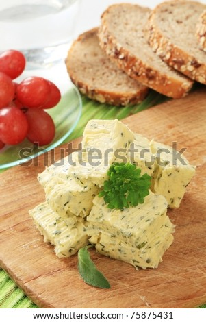 Stick of fresh herb butter on a cutting board - stock photo