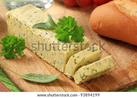 Stick of fresh herb butter on a cutting board