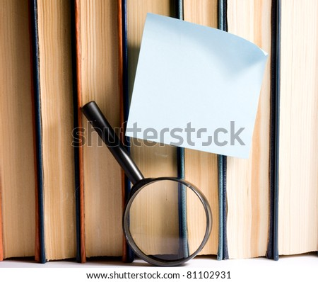 Sticker on books and magnifying glass - stock photo