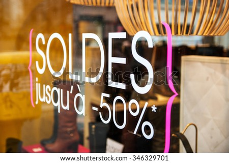 Sticker sign - Sale up to half-price 50% on french luxury store window during winter sale season - stock photo
