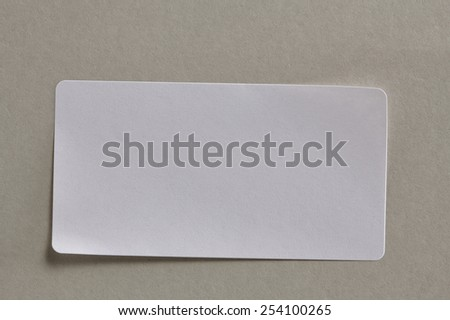Stickers Label Close Up on Cardboard Background with Real Shadow. Top View of Adhesive Paper Tag. Copy Space for Text or Image - stock photo