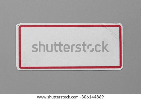 Stickers Label Close Up on Grey Background with Real Shadow. Top View of Adhesive Paper Tag with a Red Border. Copy Space for Text or Image - stock photo