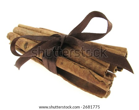 Sticks of cinnamon joined brown string on the white background - stock photo