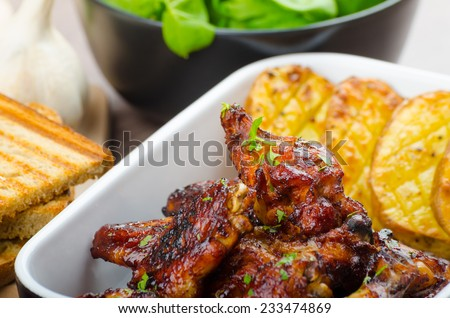 Sticky chicken wings with garlic bread panini, rustic spicy potatoes, fresh spinach leaves - stock photo