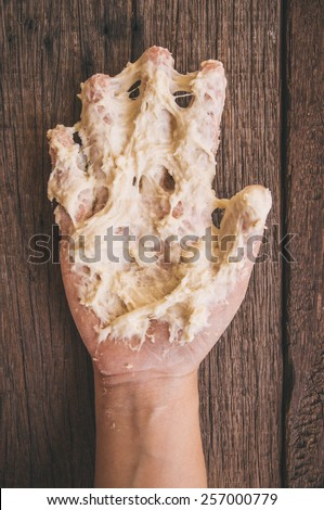 Sticky Hand Full of Dough While Kneading Dough for Making Bread, Pizza and Others Pastry. Concept and Idea of Homemade Fresh Baking. Vintage Rustic Style. / Wood Table Background. - stock photo