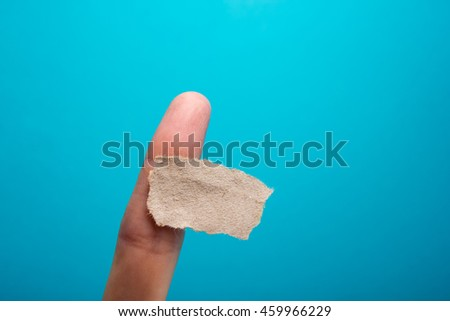 Sticky note, finger up of thumb, yellow reminder on blue background. - stock photo