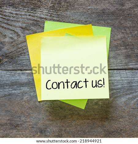 Sticky note on a wooden wall with the words Contact Us on it - stock photo