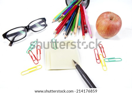 Sticky note, pen, glasses, crayon, and apple, isolated on white background - stock photo